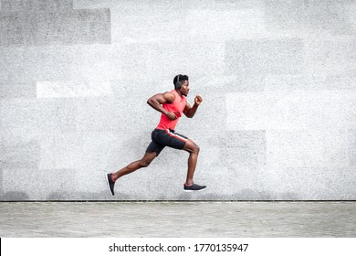African American guy runner runs fast forward against the background of the city wall, sports man train on the street, general plan