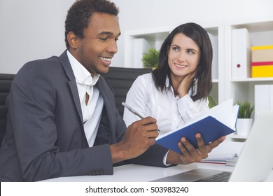 African American guy is smiling and looking at his notes. His colleague is looking at him with love. Concept of business relationships