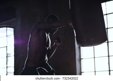 An African American guy trains in a vintage gym and fists his boxing bag fists. Concept of: gym, fitness, boxing, success, workout and power