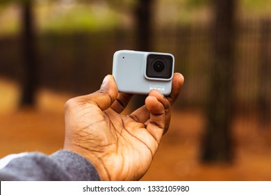 African American hands holding a GoPro Hero 7 white action camera in fall setting in Baton Rouge, Louisiana USA - December 31 2018