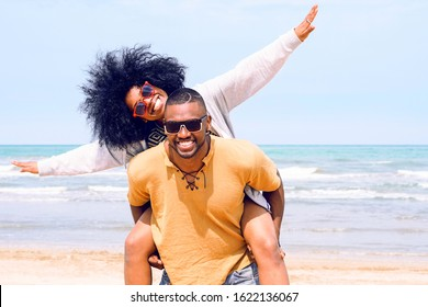 African american happy couple having fun piggyback riding and playing airplane on the beach - Black man and afro hair woman in playful moment on the shore at summer time - Concept of happiness image