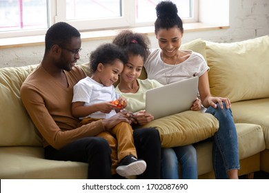 African american happy family with two children having good time using laptop. Young diverse smiling husband and wife with cute daughter and son sitting on couch at home looking at computer.