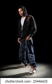 African American hip hop dancer standing over a dark background