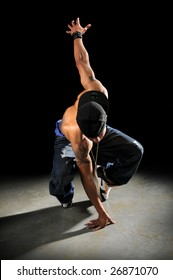 African American hip hop dancer performing over a dark background