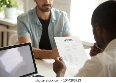 African american hr manager holding applicants curriculum vitae at job interview, black recruiter or employer considering cv of caucasian vacancy candidate during hiring negotiations, focus on resume