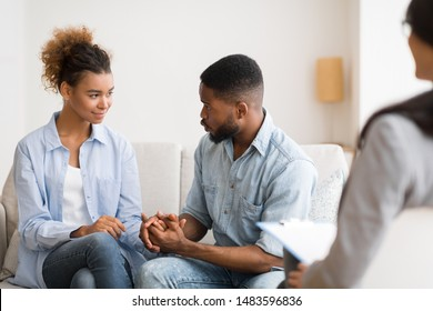 African American Husband Apologizing And Making Up With Wife After Quarrel At Couples Psychologist's Office. Selective Focus