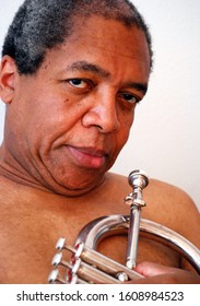 African american jazz musician holding his flugel horn.