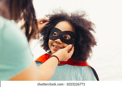 African American kid being supported and helped by supportive mother for little adventure and protection