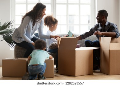African american kids helping parents unpacking boxes in living room together, afro parents and mixed race children packing stuff preparing to relocate, black family in new home on moving day