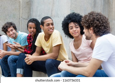 African american and latin young adults talking about politics outdoor in the summer