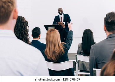 african american lecturer talking to audience during seminar in conference hall, participant raising hand