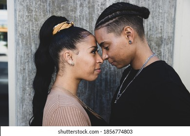 African American lesbian couple touching foreheads in tender mom