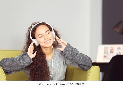 African American listening to music in headphones in green armchair