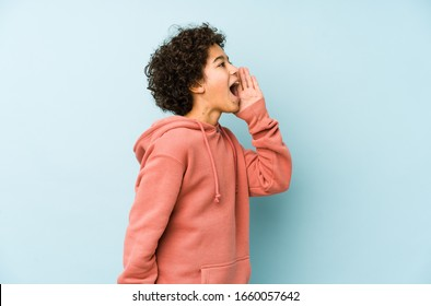 African american little boy isolated shouting and holding palm near opened mouth.