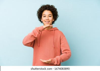 African american little boy isolated holding something with both hands, product presentation.