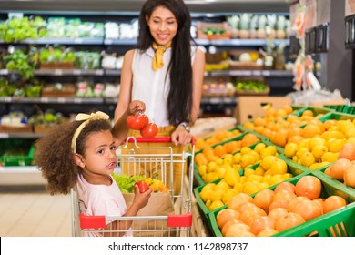 african american little child sitting in shopping trolley while her mother carrying it near fruit department in supermarket