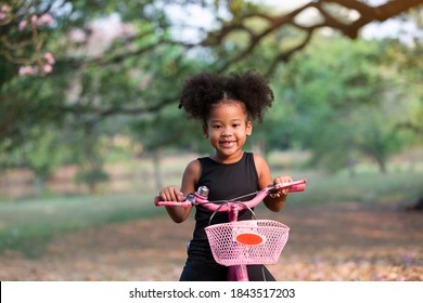 African American little curly cute girl riding bicycle in the park. Kid playing with bicycle in garden