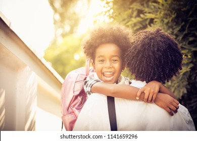 African American little girl in fathers hug. Looking at camera. Close up.
