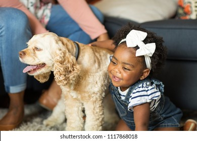 African American little girl and her mom playing with thier dog.