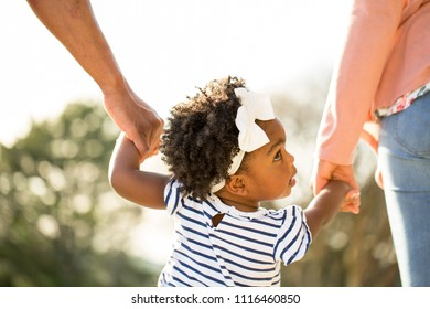 African American little girl holding hands with her parents.
