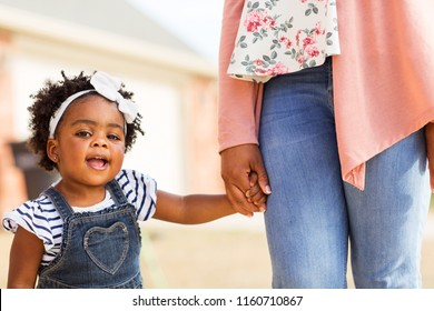 African American little girl holding her mothers hand.