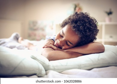 African American little girl sleeping in bed. Space for copy.