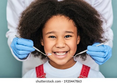 African American little girl with a toothy smile during an inspection of oral cavity by a dentist. Child in a dental clinic for children, cropped
