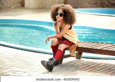 African American  little girl wearing stylish clothes by the pool. Fashion kid concept