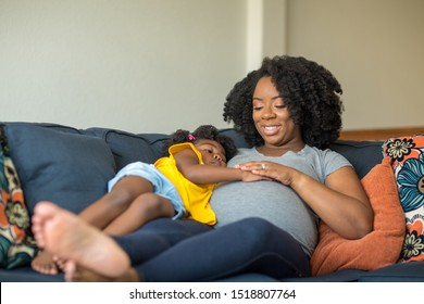 African American llittle girlh olding her mother's stomach.