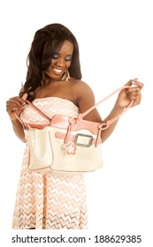 An African American looking down into her bag with a smile.