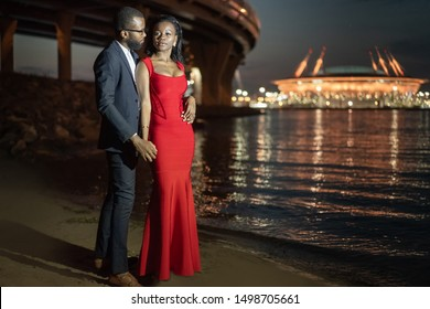 African American lovers on a night beach. A man hugs a woman. Black lovers look at each other. Date in the night city. Walk along the night beach. Husband and wife after a party. African couple.