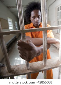 An African American male with an afro making various faces and gestures inside a federal prison
