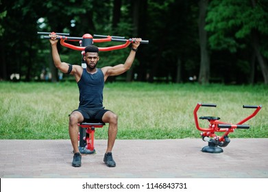 African american male athlete sport man with running sports arm case for mobile phone, doing exercises on the street workout simulators.