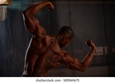 African American male body builder posing on a black background in studio setting. Back view
