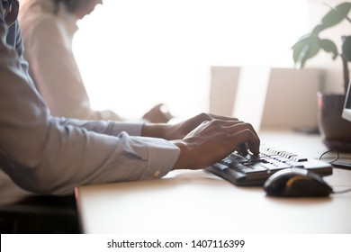 African american male company employee working on computer typing on keyboard sitting at office desk, corporate information online technology and pc business software close up view of hands on device