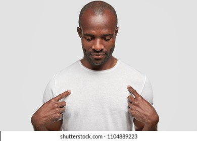 African American male with dark skin indicates at white t shirt, shows place for your design or logo, keeps head down, advertises new clothes, isolated on white background. People and advertisement