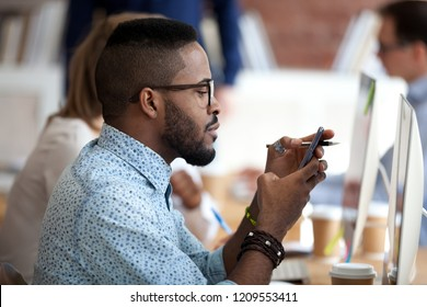 African American male employee in glasses busy with smartphone texting message to friend, serious black worker using cell phone at work browsing internet or checking email or social medias