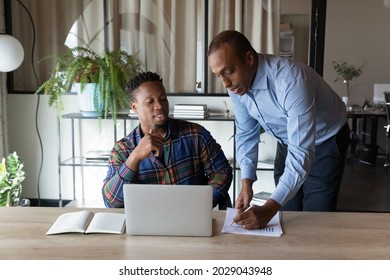 African American male employees brainstorm discuss company financial business ideas working on computer in office. Ethnic men colleagues negotiate over paperwork use laptop. Teamwork concept.