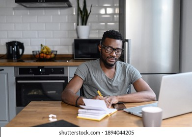 African american male freelancer sitting at the desk, look at the laptop screen. Happy young student taking notes, remotely studying. Successful business man searching ideas, working on project