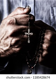 African American male hands praying holding a beads rosary with Jesus Christ in the cross or Crucifix on black background. Mature Afro American man with Christian Catholic religious faith