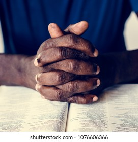 African American male hands resting on an open bible