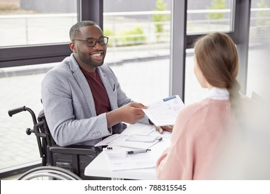 African American male invalid sits at workplace in wheelchair, shares creative ideas and opinions with female worker, demonstrate new business project have informal meeting. Physically handicapped man