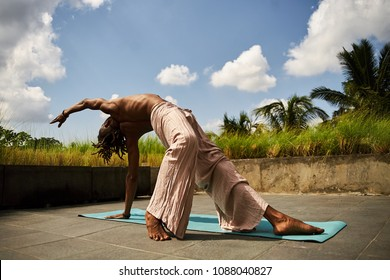 African American male practicing yoga on a rooftop on a sunny day
