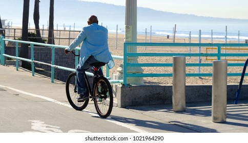 An African American male riding his bicycle in the morning along Manhattan Beach