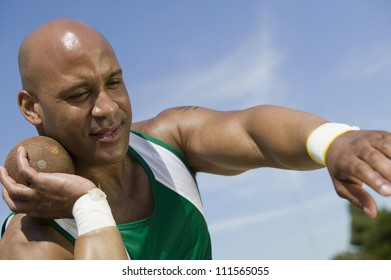 African American male shot putter ready to throw metal ball