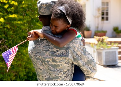 African American male solider wearing uniform holding and hugging his daughter with a USA flag, standing by the house on a sunny day.