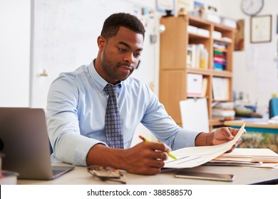 African American male teacher working at his desk