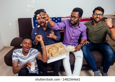 african american males eating pizza and popcorn , cheering and smiling while watching TV match at home.