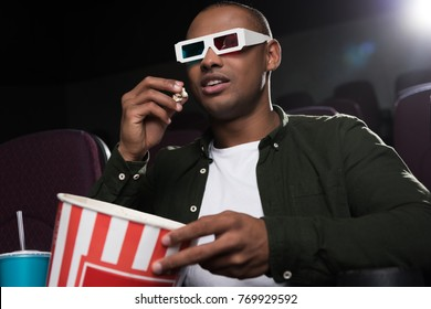 african american man in 3d glasses eating popcorn and watching movie in cinema