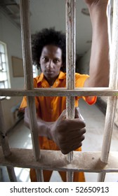 A african american man with an afro is behind a prison gate and holding on to the bars. Vertical shot.